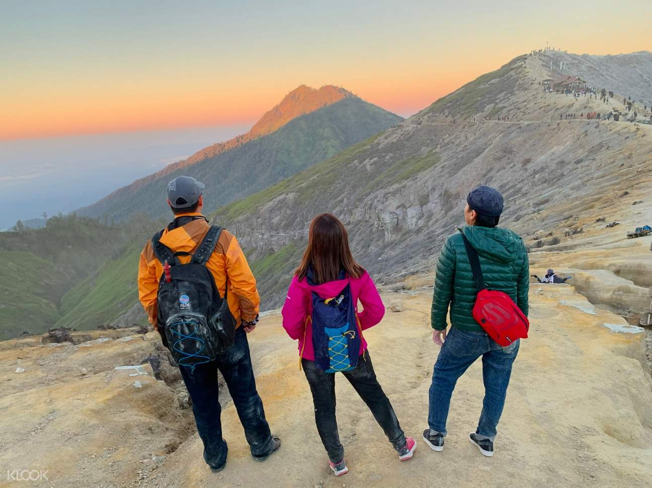 three people admiring the sunrise view