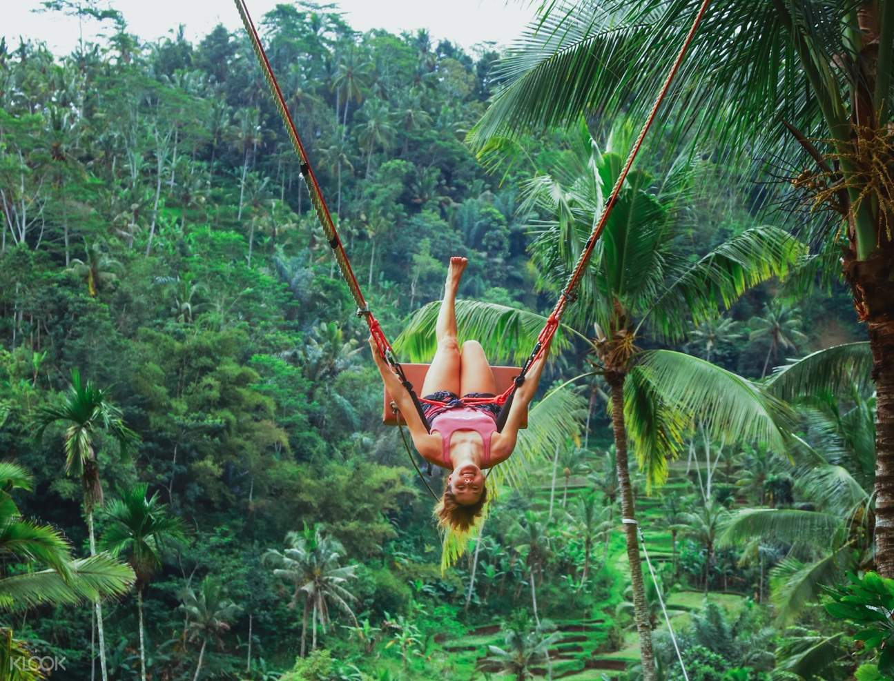 girl posing upside down on jungle swing in bali