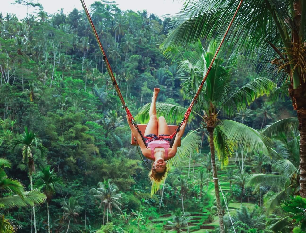 woman upside down posing on the bali jungle swing