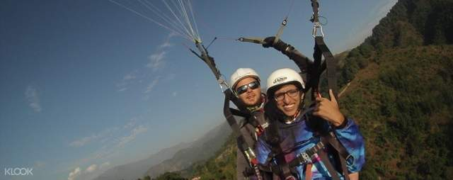 Man doing a thumbs up as he enjoys paragliding with his pilot guide