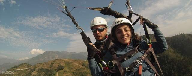 Woman with legs up enjoying paragliding with her pilot guide