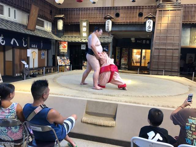 a tourist facing a sumo wrestler in a ring