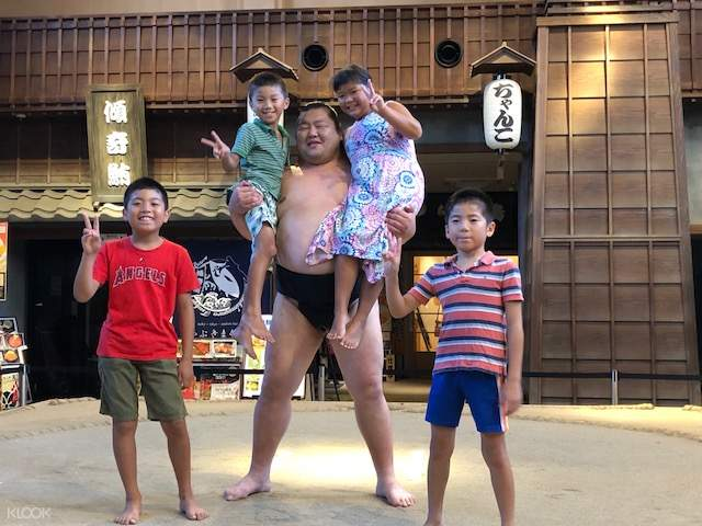 kids being lifted up by a sumo wrestler