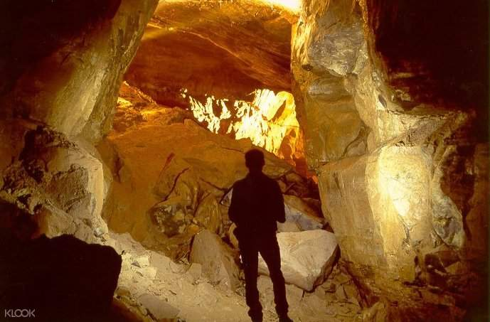 A man standing in front of a cave dwelling