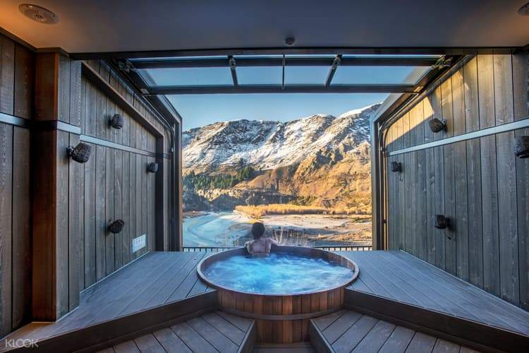 onsen hot pool with view of shotover canyon and two towels