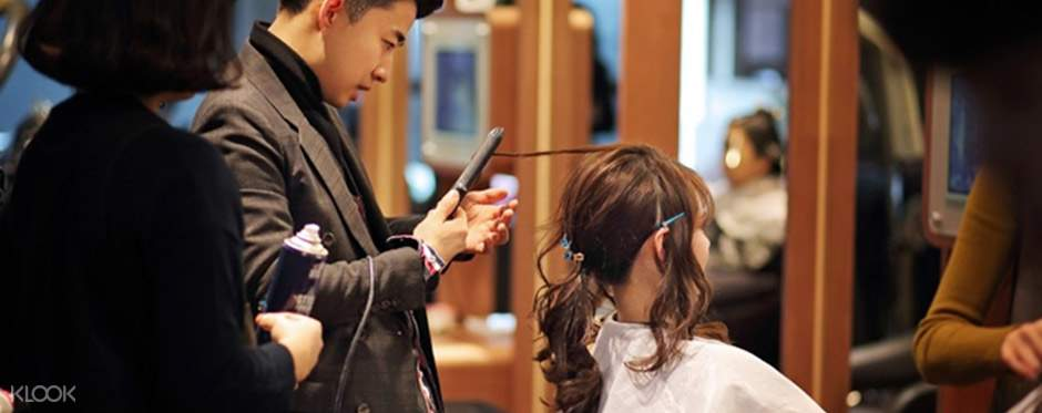 professional hairstylist curling customer's hair