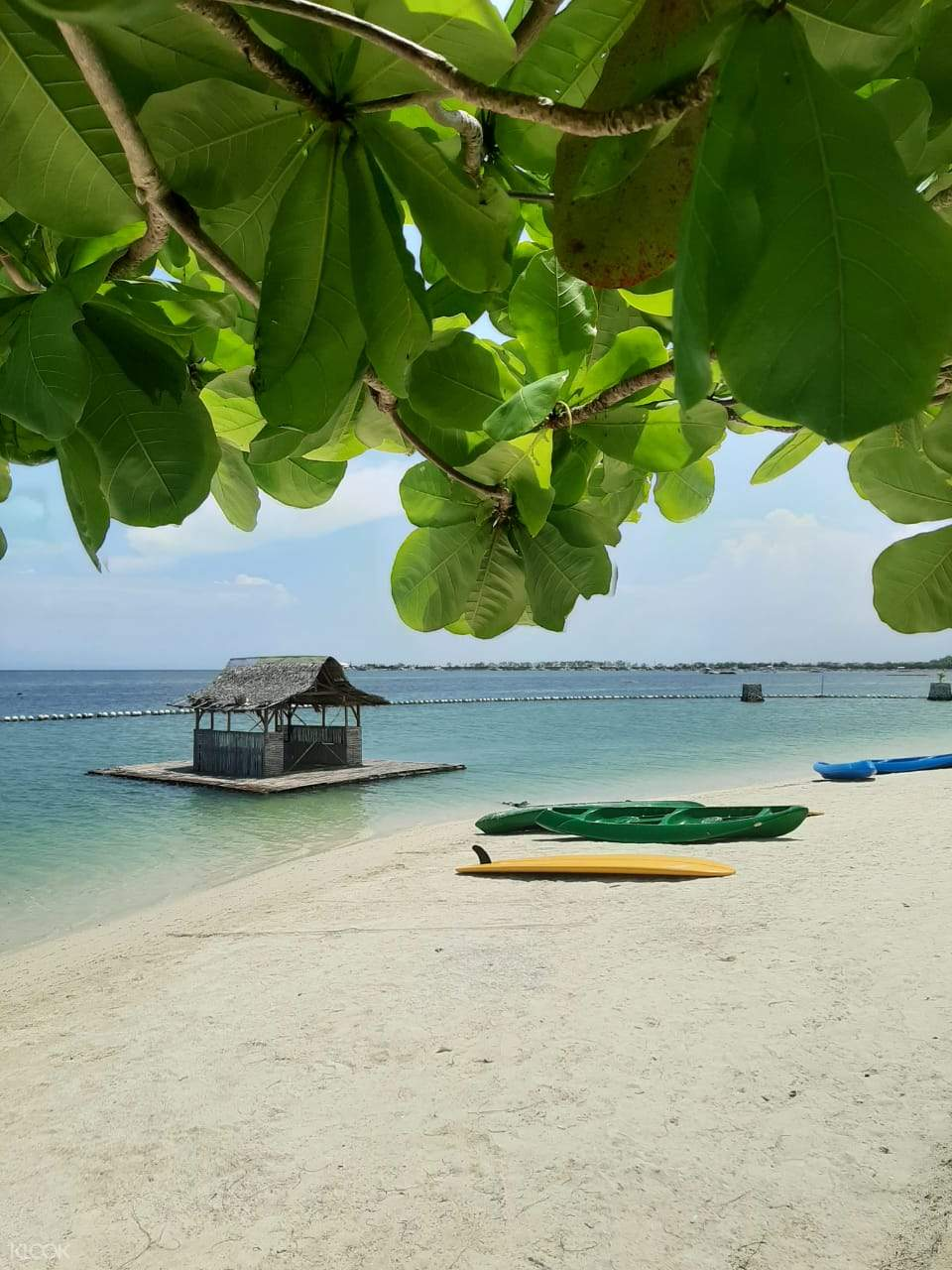 Solea Mactan's beachfront area with paddle boats and a surfboard
