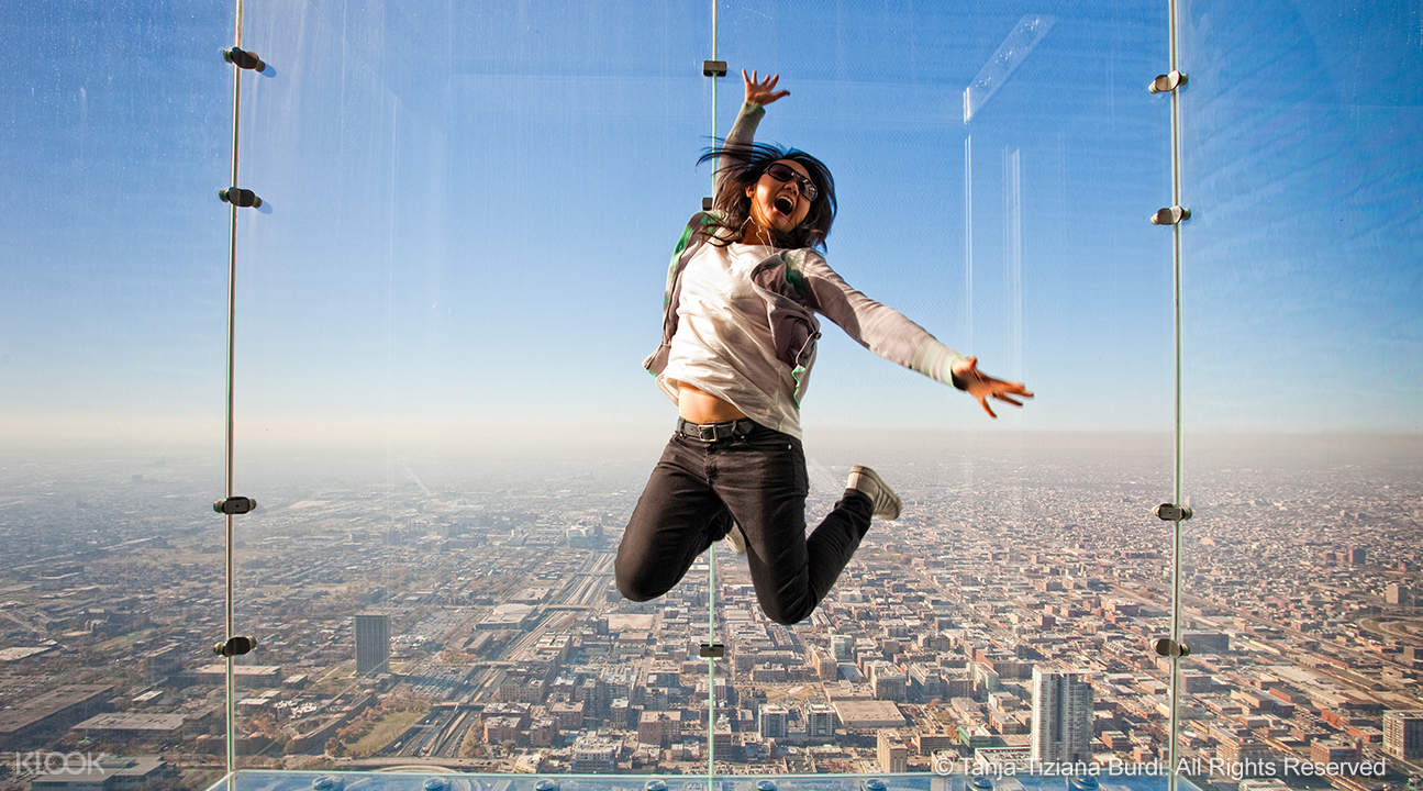 a woman posing for a jump shot in Skydeck Chicago