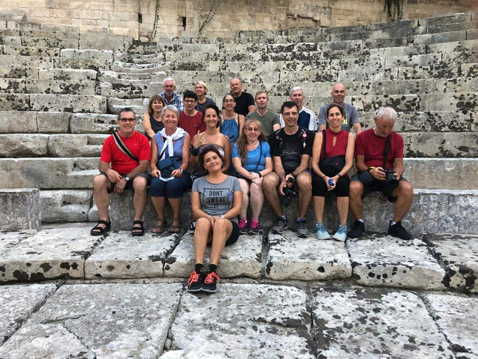tour group sitting on stone stairs in lecce