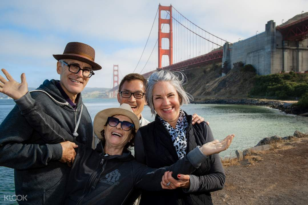people posing for a photo with the Golden Gate Bridge in the background