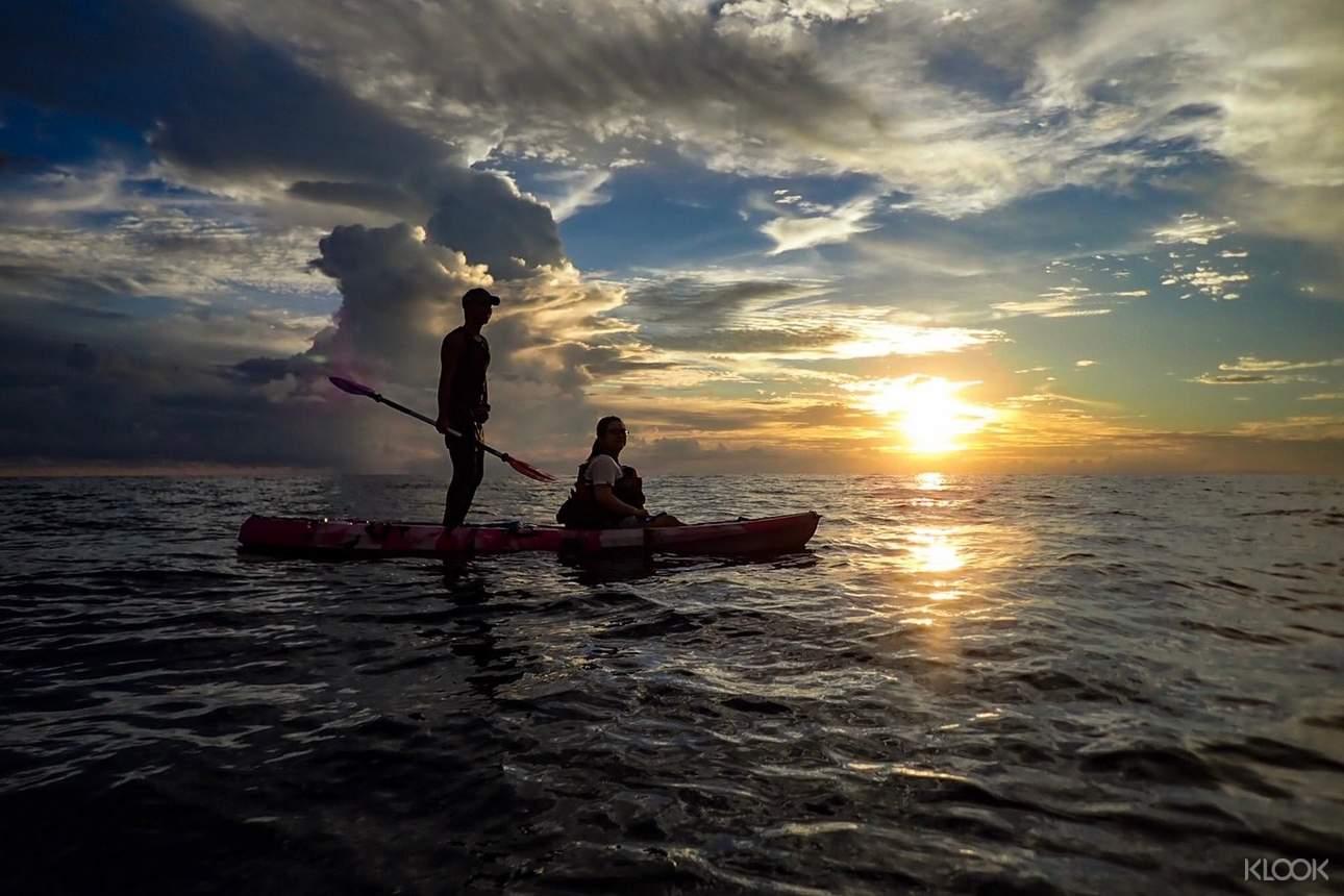 一邊划在水面上,一邊欣賞天空中緩緩升起的太陽美景